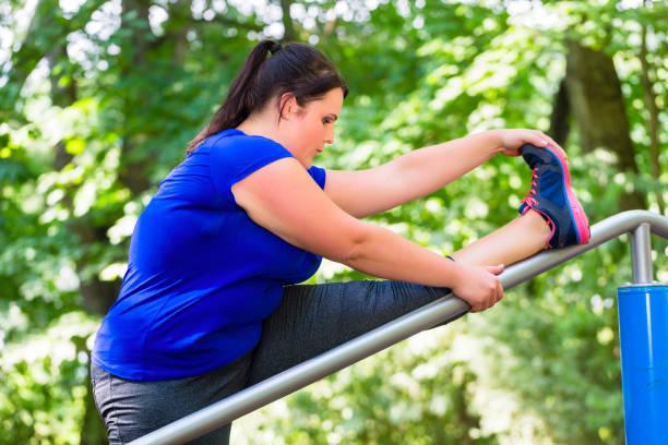 beleibte frau tut sport stretching im freien im park - damen sporthose übergröße stock-fotos und bilder