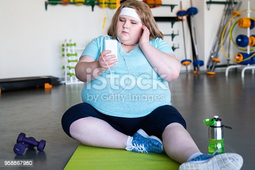 Full length portrait of obese young woman sitting on yoga mat on floor and listening to music ready to start fitness workout