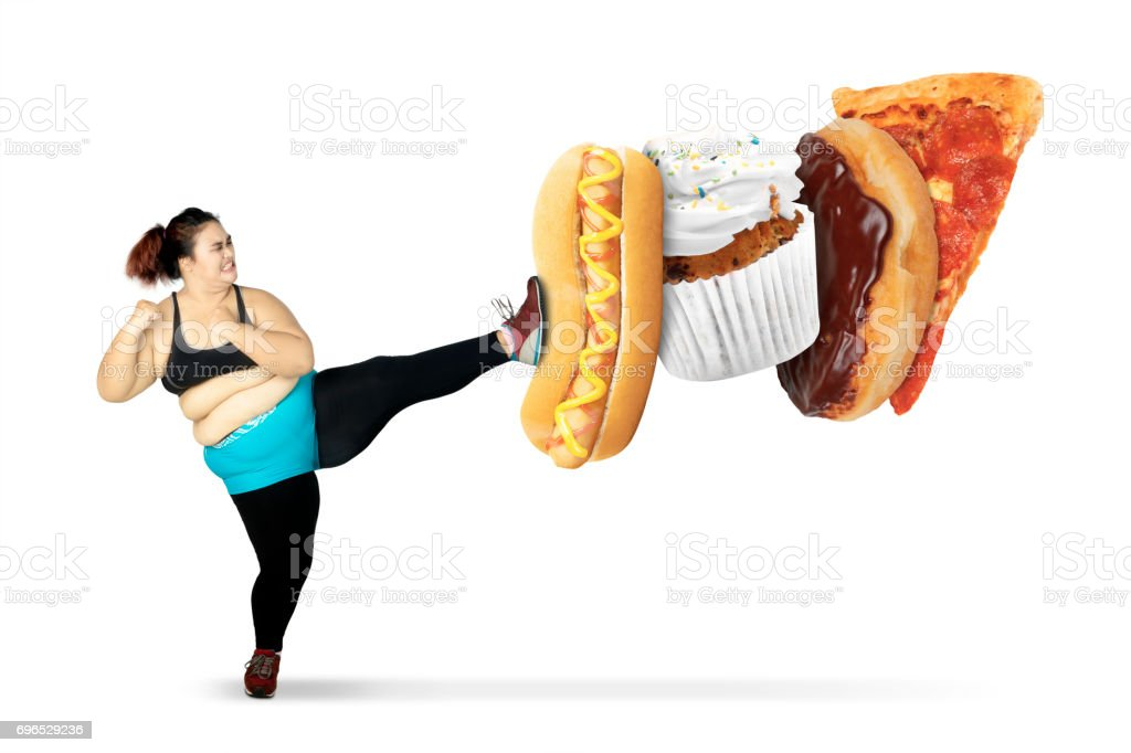 Obese woman kicks junk foods stock photo