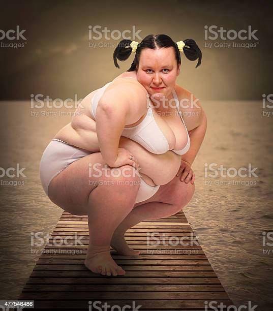 Obese woman dressed in bikini posing on a pier over sea. Warm filtered look.
