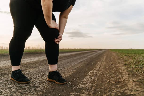 Obese woman touching paining leg. Joints overload stock photo