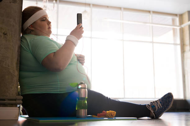 Übergewichtige Frau mit Smartphone nach Training – Foto