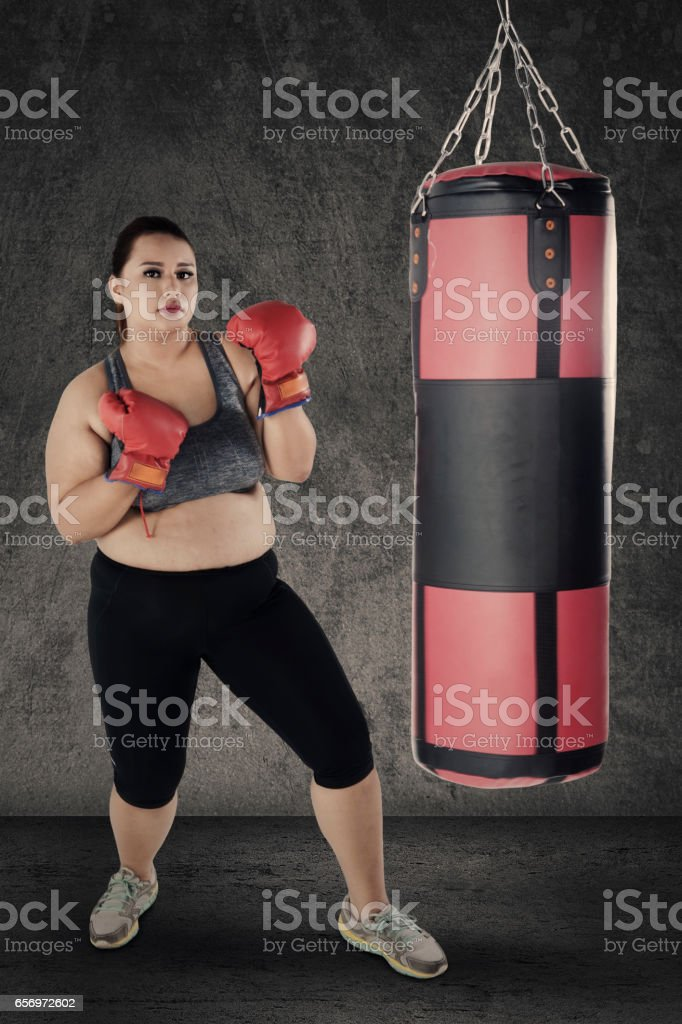 Obese woman with boxing gloves and sack stock photo