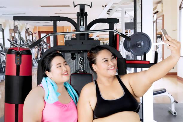 zwaarlijvige vrouwen met smartphone in sportzaal centrum - call center stockfoto's en -beelden