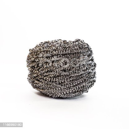 Object for cleaning. Household goods. Grater scraper metal abrasive tangle for washing dirty kitchen utensils from spiral wire on a white background