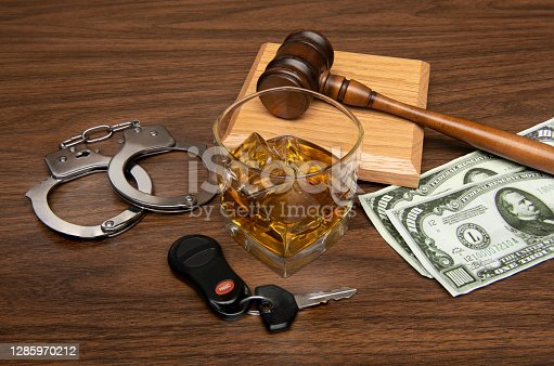 A whiskey drink with car keys ,handcuffs, gavel and a pair of one thousand dollar bills on tabletop background
