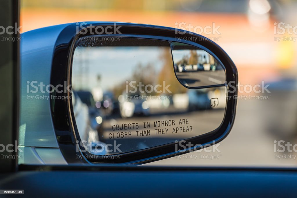 Objects in mirror are closer than they appear on car stock photo