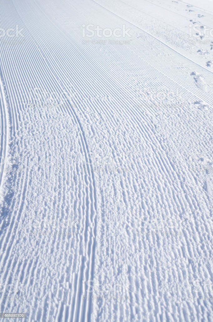 Oblique strips of snowcat and traces on white snow stock photo