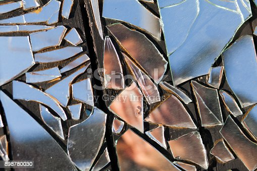 istock obscured image of a woman in broken glass reflection 898780030