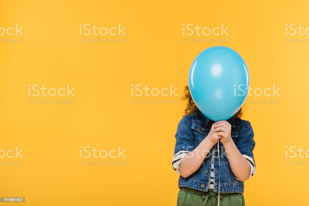 obscured view of child covering face with balloon isolated on yellow stock photo