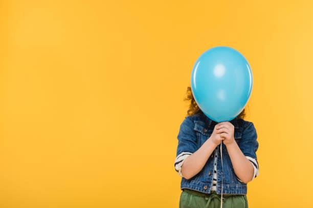 het oog wordt onttrokken weergave van kind die betrekking hebben op gezicht met ballon geïsoleerd op geel - verduisterd gezicht stockfoto's en -beelden