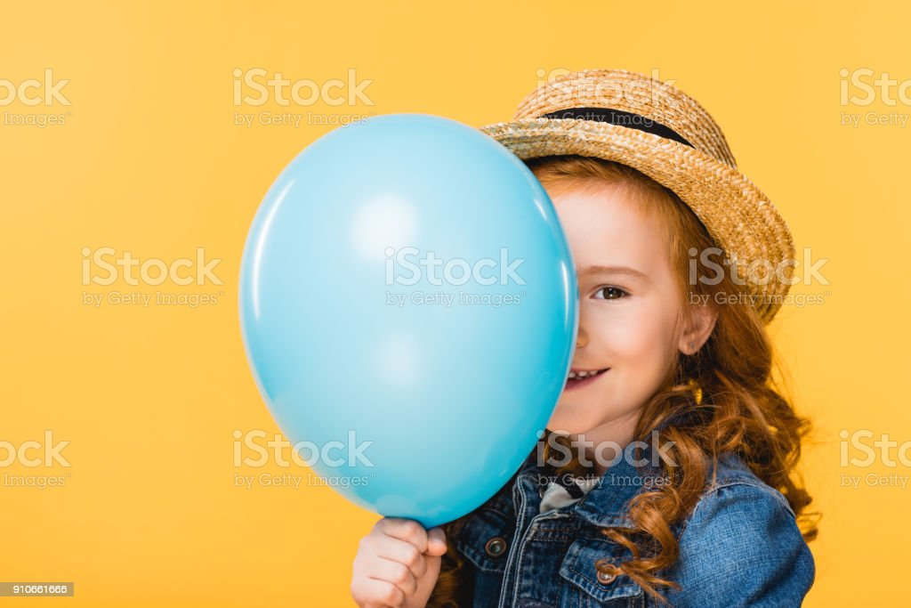 obscured view of smiling child covering face with balloon isolated on yellow stock photo