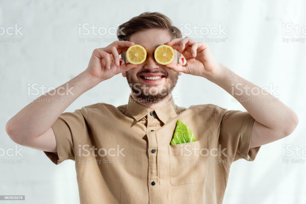 visão obscurecida do homem sorridente com pedaços de limão e folha de repolho de savoy no bolso, conceito de estilo de vida vegan - Foto de stock de Adulto royalty-free