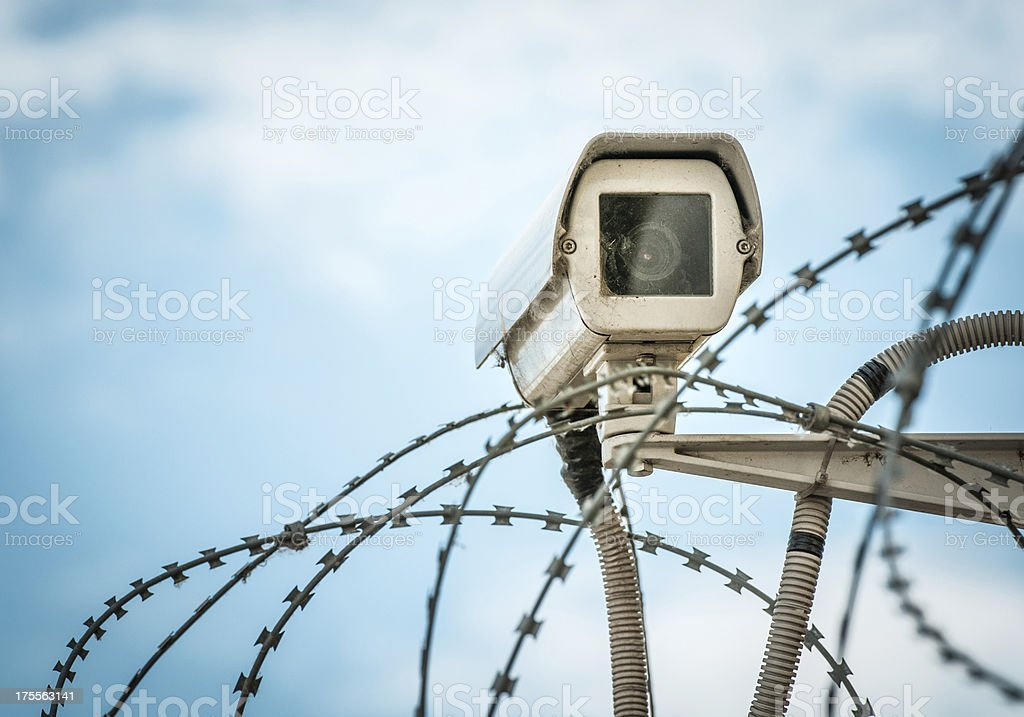 Observation camera and barbwire on blue sky. royalty-free stock photo