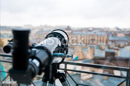 Professional telescope of black color by window with urban scene behind it