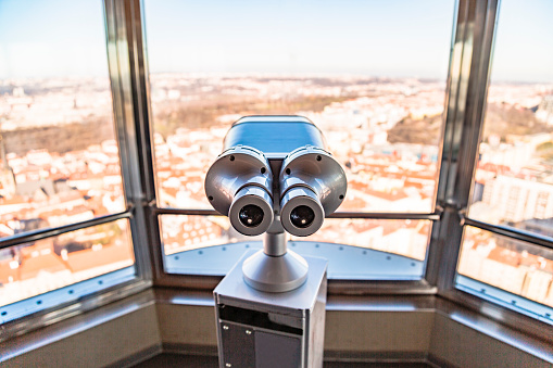Observation telescope in Prague against window with panorama