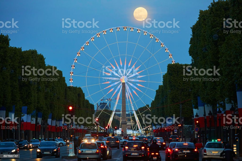 Observation wheel on Champs-Elysees street with full moon in Paris stock photo