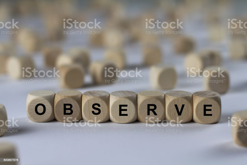 observe - cube with letters, sign with wooden cubes stock photo