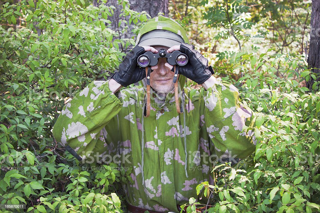 Observer in the woods Conducted covert surveillance in the forest reserve Camouflage Stock Photo