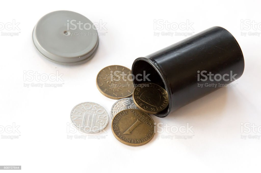 Obsolete Austrian coins in a old film container stock photo
