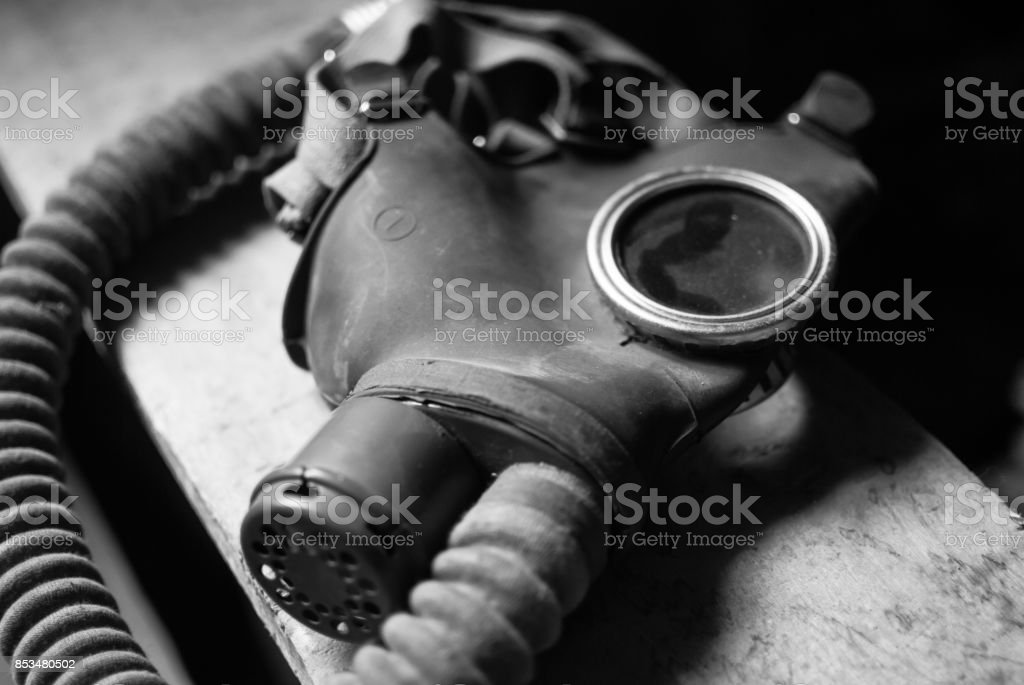 Obsolete retro gas mask laying on the wooden stairs. stock photo