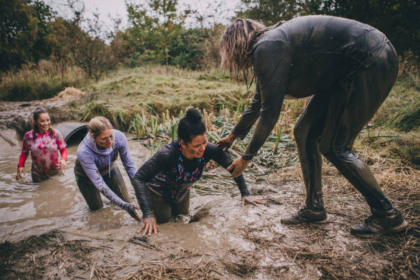 Obstacle Course Support Women are taking part in a charity obstacle course. They are wading through a muddy ditch and one of the women is standing and helping them get out. obstacle course stock pictures, royalty-free photos & images