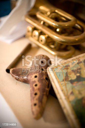 Small ocarina instrument (hand made product) and a trumpet in background.