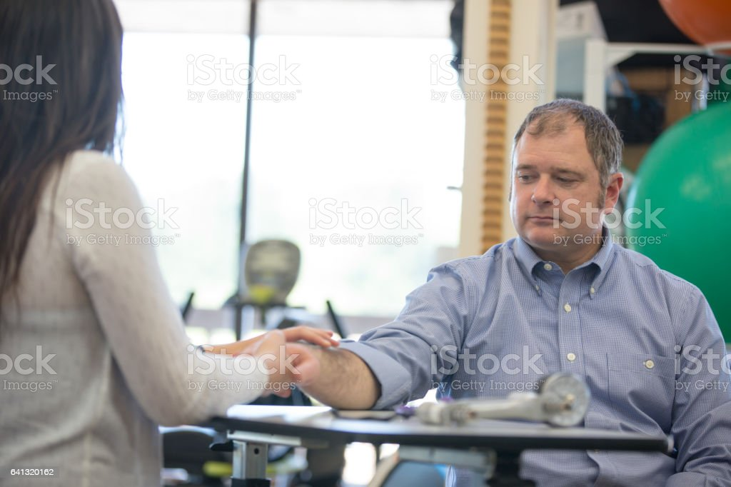 Occcupational therapist helps man with hand exercises stock photo