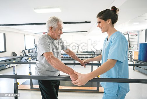 istock Occupational therapist and senior patient using the parallel bars to walk 912334126