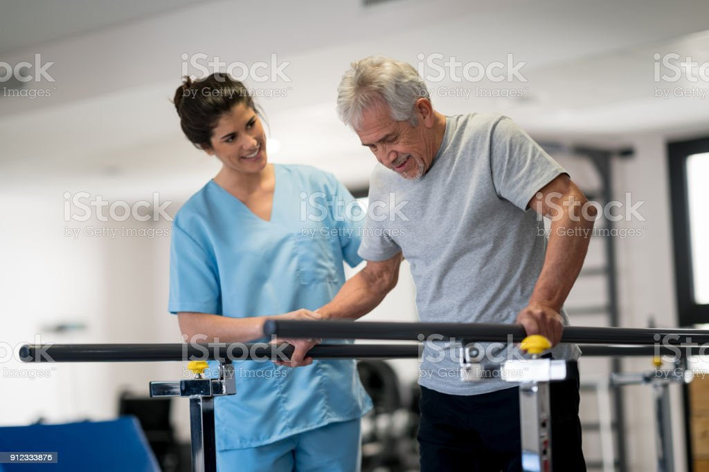 Occupational therapist and senior patient working out using parallel bars to walk stock photo