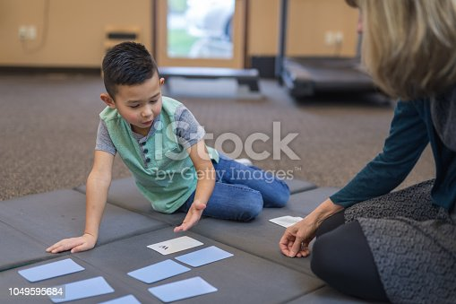 An occupational therapist works with a handsome elementary-age ethnic boy on his memorization skills. She is sitting on the floor with him and showing him a fun matching game to play with memory cards.