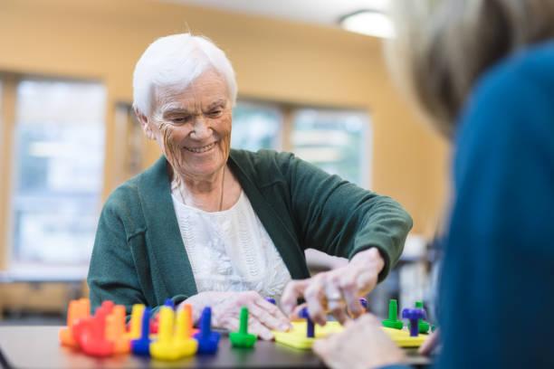terapeuta ocupacional trabaja con una mujer mayor - geriatría fotografías e imágenes de stock