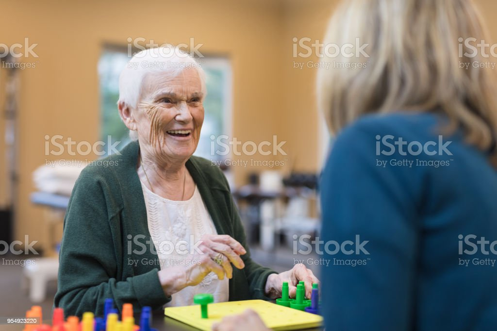 Occupational therapist works with an elderly woman stock photo