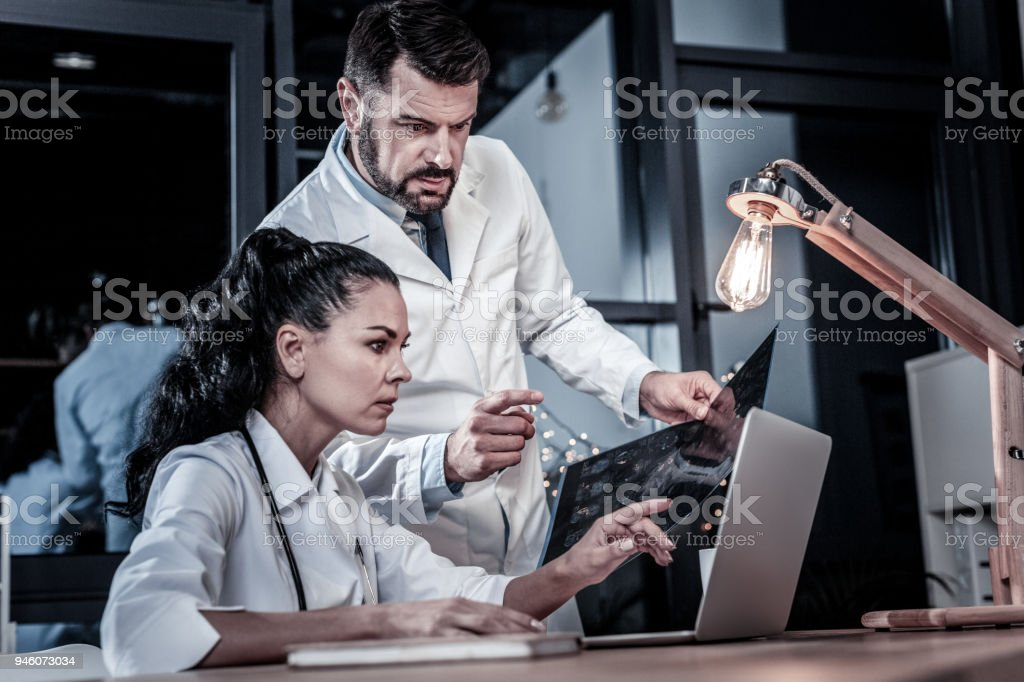 Occupied qualified doctors working together and looking at the laptop. stock photo