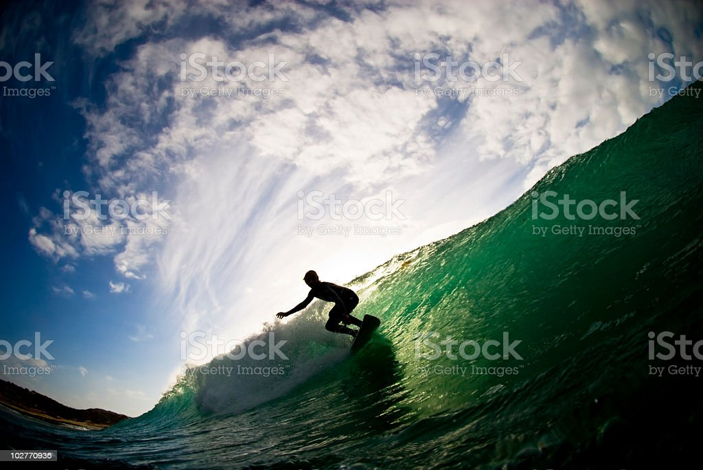 Ocean and cloudy sky with silhouette of surfer stock photo