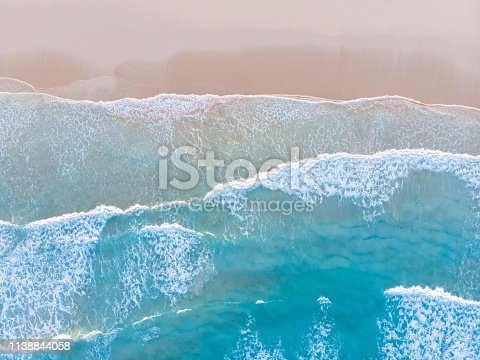 istock Ocean beach aerial top down view with blue water, waves with foam and spray and fine sand, beautiful summer vacation holidays destination 1138844058