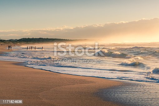 Ocean beach at sunrise with unrecognizable people doing sports. Beach lifestyle