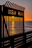 The stunning sunsets of Southern California routinely silhouette the gate and sign to San Diego's Ocean Beach.