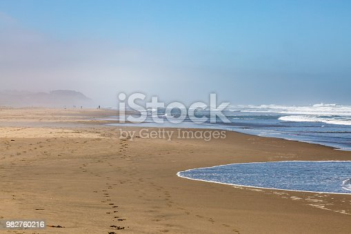 The vast sandy Ocean Beach in San Francisco, with a mist in the distance