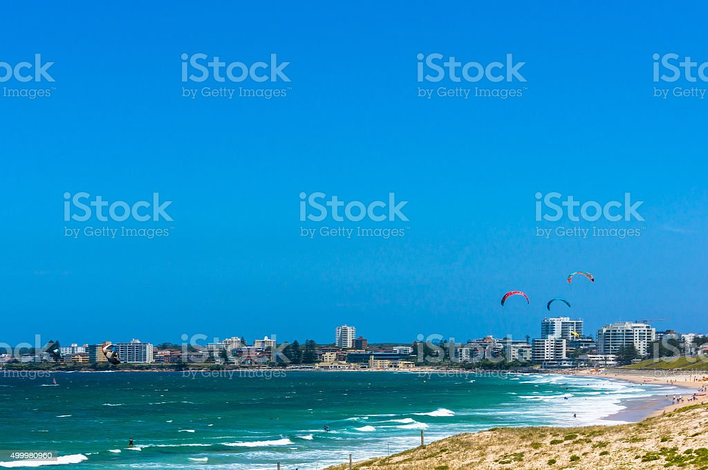 Ocean beach with kitesurfers and city skyline in a distance stock photo