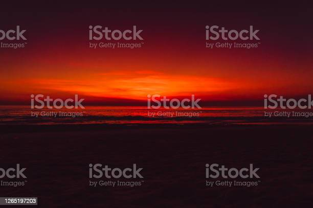 Photo of Ocean beach with waves and reflection at bright sunset or sunrise in Bali.