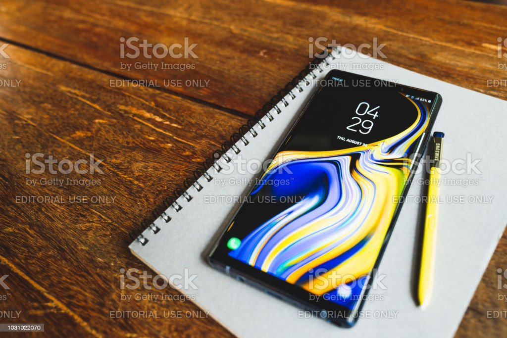 Ocean Blue Samsung Galaxy Note 9 with yellow S pen stylus on a notebook with copy space on wooden table. Illustrative Editorial. stock photo