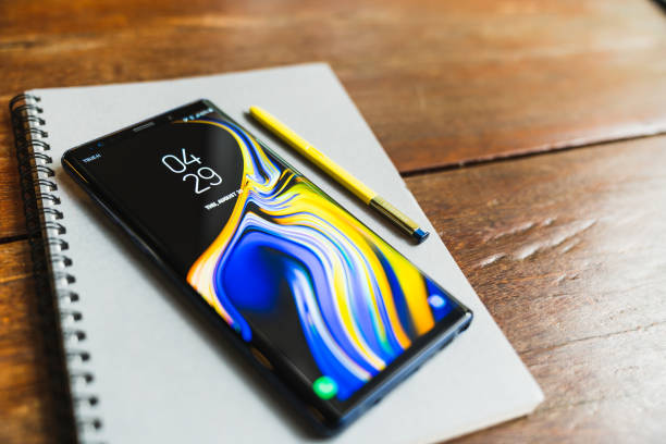 Ocean Blue Samsung Galaxy Note 9 with yellow S pen stylus on a notebook with copy space on wooden table stock photo