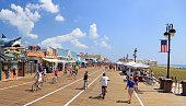 Ocean City, New Jersey - August 05, 2018:  People walking and biking along the boardwalk in Ocean City, New Jersey, USA