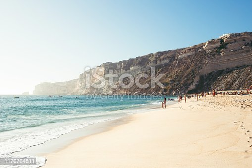 Ocean coastline with waves, people and cape. Summer background.