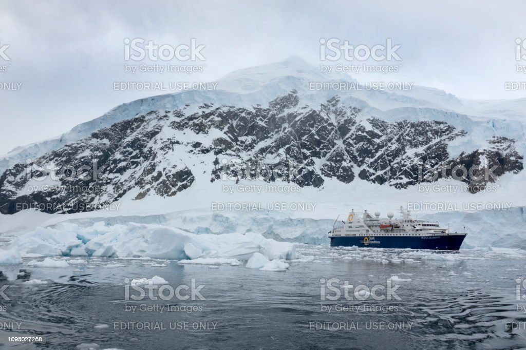 Ocean Diamond ship cruises ice filled Neko Harbor Antarctic Peninsula mountain glaciers Antarctica stock photo