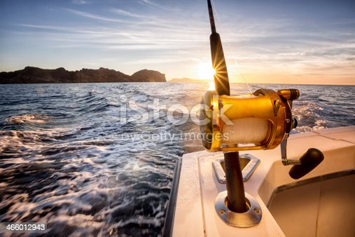 Big fishing reels on a boat in the ocean.  These reels are used to catch big game fish such as Mahi-mahi, dorado, tuna, sailfish, swordfish sharks and marlin.  They are used in tropical and cold water oceans.