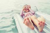 Cute little girl plays on a pool float in the ocean