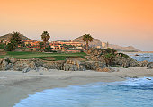 A golf green hugging the sea in the tropics. Themes include resort, golf, mexico, tropics, ocean, sea of cortez, scenic, golf green, sand, beach, nobody, palm trees, and fairway. Nobody is in the image.