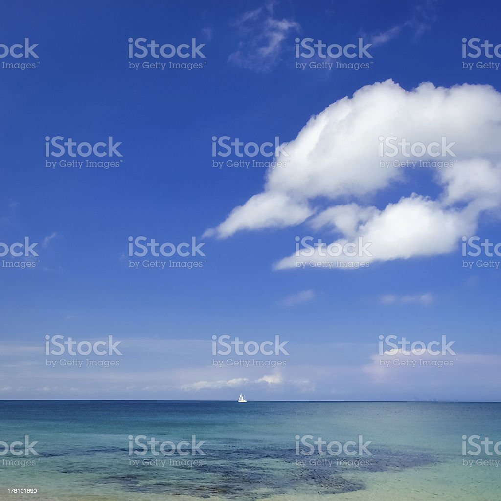 Ocean landscape with blue cloudy sky and sailboat royalty-free stock photo